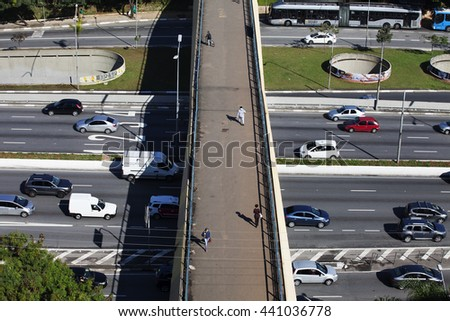 SAO PAULO, BRAZIL - June, 8, 2016: Top view of some people crossing a footbridge over 23 de Maio Avenue, a famous road at Sao Paulo, Brazil.