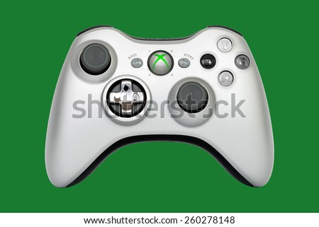 SAO PAULO, BRAZIL - MAR 13, 2014: The wireless gamepad for the Xbox 360, a home video game console produced by Microsoft, isolated on dark green background. - stock photo