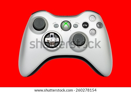 SAO PAULO, BRAZIL - MAR 13, 2014: The wireless gamepad for the Xbox 360, a home video game console produced by Microsoft, isolated on red background. - stock photo