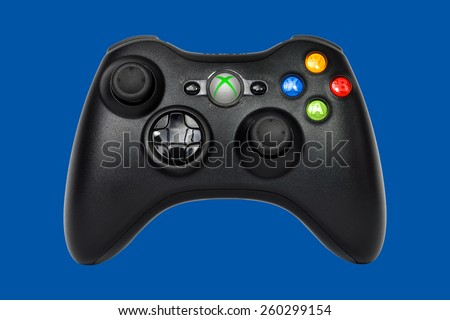 SAO PAULO, BRAZIL - MAR 13, 2014: The wireless gamepad for the Xbox 360, a home video game console produced by Microsoft, isolated on dark blue background. - stock photo