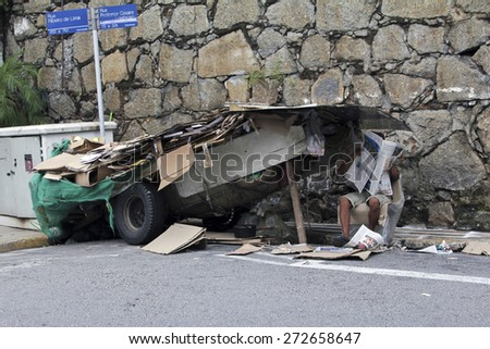 SAO PAULO, BRAZIL - MARCH 8, 2015: An unidentified recycling paper collector with his hand made car in the streets of Sao Paulo Brazil.