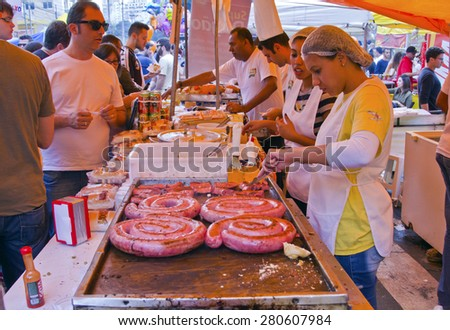 SAO PAULO, BRAZIL - MAY 17, 2015: An unidentified group of people in the hand made sausage sandwich stand in street fair market in Sao Paulo.  - stock photo
