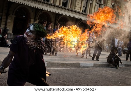 "SAO PAULO, BRAZIL - SEPTEMBER 17, 2016: Street artist dressed as Batman's character ""The Joker"" presents fire performance in front of Luz train station, in downtown Sao Paulo"