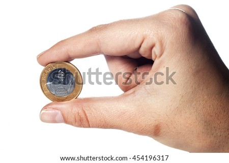 SAO PAULO, SP/BRAZIL, JUNE 28, 2016:  Commemorative coin of Brazil. An adult hand holding an one real coin isolated on white background. Illustrative editorial image.