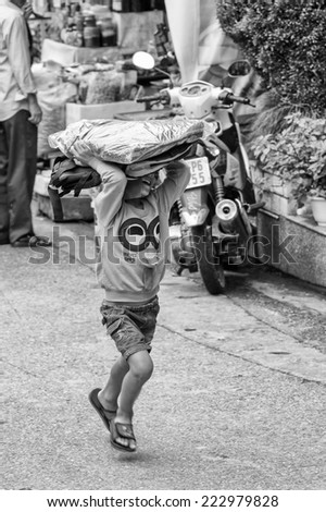 SAPA, VIETMAN - SEP 12, 2014: Unidentified Vietnamese boy carries stuff on his head in the street in Sapa, Vietnam. 86% of Vietnamese people belong to the Viet ethnic group - stock photo