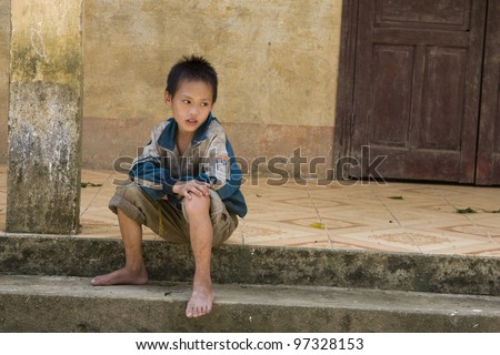 SAPA VIETNAM - AUGUST 28: unidentified young boy of Red Dao ethnic minority waits in front of school, on August 28, 2011, in Sapa, Vietnam. Red Dao tribe is one of the minority tribes in Sapa, Vietnam