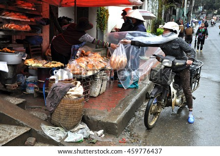 SAPA, VIETNAM - FEBRUARY 22, 2013: Woman selling fresh pastry products, bread and spring rolls in the rural market of Sapa, Northern Vietnam