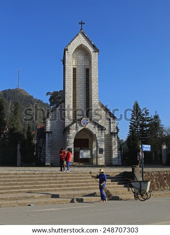 Sapa, Vietnam - Jan 15, 2015: Cleaner cleaning the side walk on the sidewalk of the square in front of the Catholic Holy Rosary church in Sapa town, Lao Cai province, Vietnam.