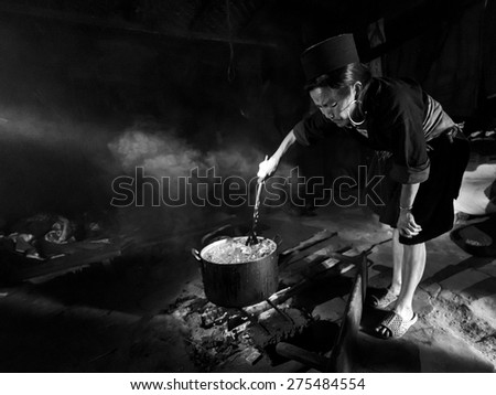 SAPA, VIETNAM - MARCH 18: Unidentified minority tribe of a elderly woman cooking corn food for the domestic animals inside her home on March 18, 2015 of Sapa, Vietnam.