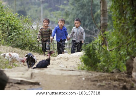 SAPA, VIETNAM - NOV 21: Three unidentified Vietnamese children walk in hills of Sapa, Vietnam on November 21, 2010. Vietnam's 2011 population is 90,549,390 with 25% of the population age 14 and under