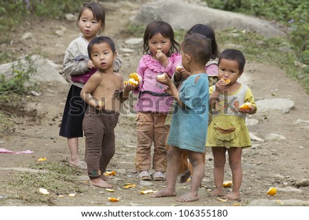 SAPA, VIETNAM- NOVEMBER 21: Six unidentified Vietnamese children play and eat in Sapa, Vietnam on November 21, 2010. Vietnam's 2011 population is 90,549,390 with 25% of the population age 14 and under - stock photo