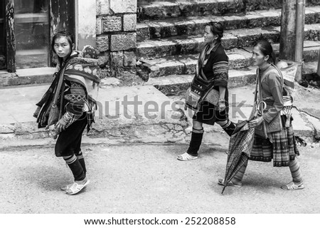 SAPA, VIETNAM - SEP 22, 2014: Unidentified Hmong woman in traditional clothes walks in Sapa. Hmong is on of the minority eethnic group in Vietnam