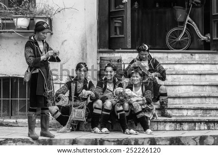 SAPA, VIETNAM - SEP 20, 2014: Unidentified Hmong women in a traditional costume trying to sell diffenrent stuff. Hmong people is a minority ethnic group living in Sapa