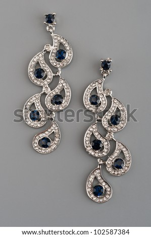 Sapphire beautiful woman earings on gray background - stock photo