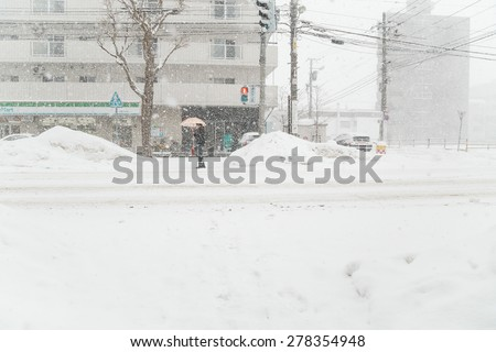 SAPPORO, JAPAN - JANUARY 12, 2014: Man waiting for a green light at the crosswalk.