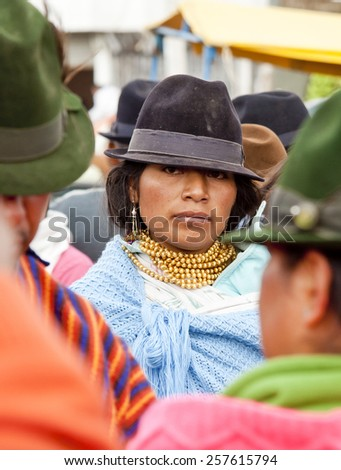 SAQUISILI, ECUADOR - MAY 18: Indian woman wearing a hat and a necklace of gold beads in the Andean market Saquisili­ on May 18, 2014 in Saquisili, Ecuador