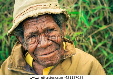 Sara village, Papua New Guinea - July 2015: Old man in yellow jacket and yellow cap looks up to photocamera and smiles nicely at Sara village in Papua New Guinea. Documentary editorial.