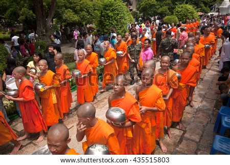 SARABURI,THAILAND -JULY 7, 2009 : Group of monks receiving flower offering from people in Tak Bat Dok Mai or Flower Offering Ceremony at Phrabuddhabat Woramahavihan Temple , Saraburi ,Thailand.