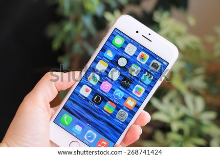 SARAJEVO , BOSNIA AND HERZEGOVINA - April 12, 2015: New gray iPhone 6 with colorful screen in woman's hand. iPhone 6 was created and developed by the Apple inc. - stock photo