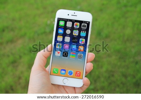 SARAJEVO , BOSNIA AND HERZEGOVINA - April 23, 2015: New gray iPhone 6 with colorful screen in woman's hand. iPhone 6 was created and developed by the Apple inc. - stock photo
