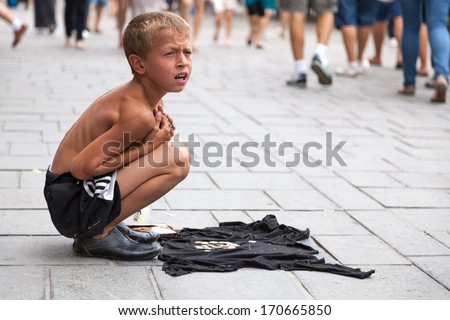SARAJEVO, BOSNIA AND HERZEGOVINA - AUG 11: Sevdalija Osmanovic, 10 years old, sings on street to bypassers on August 11, 2012 in Sarajevo, B&H. He sings in order to provide money for his family. - stock photo