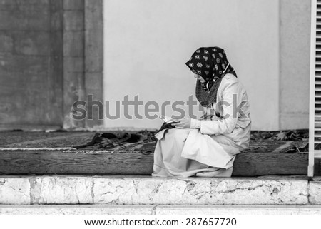 Sarajevo, Bosnia and Herzegovina - August 14, 2014: An islamic girl is reading the Quran in the main Sarajevo Mosque of Gazi Husrev-beg - stock photo