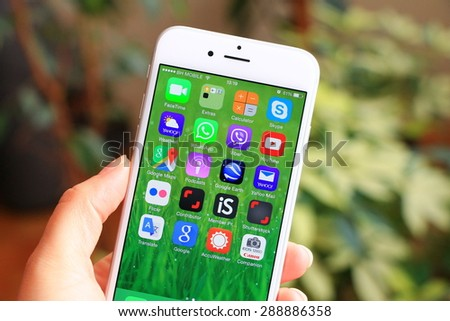 SARAJEVO , BOSNIA AND HERZEGOVINA - JUNE 13 , 2015: New gray iPhone 6 with colorful screen in woman's hand. iPhone 6 was created and developed by the Apple inc. - stock photo