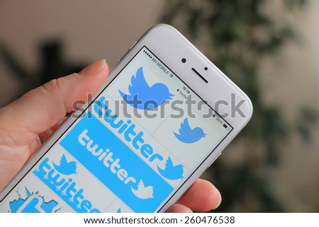 SARAJEVO , BOSNIA AND HERZEGOVINA - MARCH 14, 2015: Woman watch Twitter icons on Apple iPhone 6. Twitter is largest and most popular social networking site in the world. - stock photo