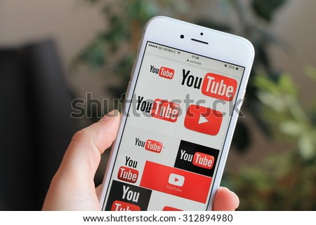 SARAJEVO , BOSNIA AND HERZEGOVINA - MAY 10 , 2015: Woman watch Youtube icons on Apple iPhone 6. YouTube is a video-sharing website. - stock photo