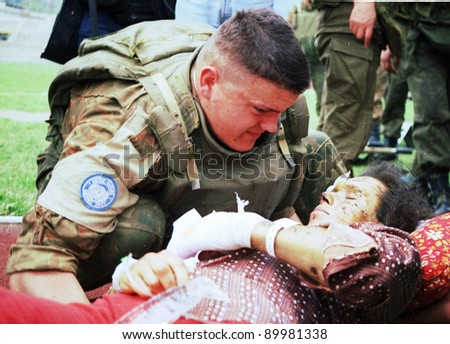 SARAJEVO, BOSNIA - APR 4: An Ukrainian soldier with the United Nations Protection Force (UNPROFOR) in Bosnia helps a wounded woman during the siege of Gorazde at a medical center in Sarajevo, Bosnia, on Monday, April 4, 1994 - stock photo
