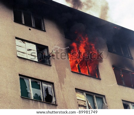 SARAJEVO, BOSNIA - MAR 18: A man attempts to put out a fire in a neighboring apartment during the final days of siege in Sarajevo, Bosnia, on Monday, March 18, 1996 - stock photo
