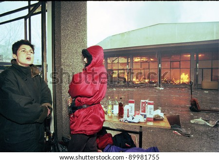 SARAJEVO, BOSNIA - MAR 18: Two women watch over their market stall while flames engulf the remaining part of the market during the final days of siege in Sarajevo, Bosnia, on Monday, March 18, 1996 - stock photo