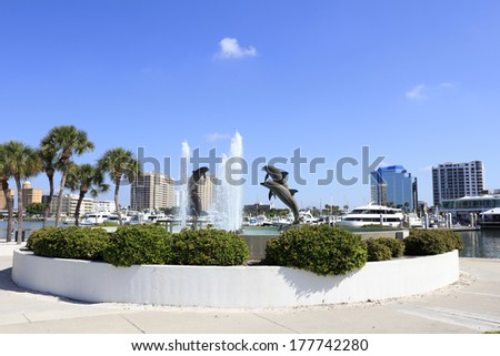 SARASOTA, FLORIDA - MAY 9, 2013: Dolphin Fountain sculpted by Steven C. Dickey, donated by Marina Jacks at the end of Sarasota Island Park and Marina with downtown buildings in the background. - stock photo
