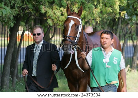 SARATOGA SPRINGS - August 30, 2008: Assistant Trainer Scott Blasi (left) walks Curlin, the 2007 Horse of the Year, before the Woodward Stakes at  Saratoga Race Track. - stock photo