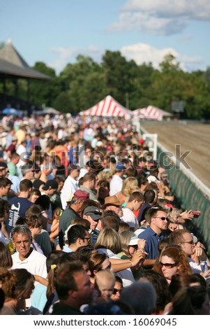SARATOGA SPRINGS - August 9: Race Fans Pack the rail in Front of the Grandstand for the Start of the Ninth Race August 9, 2008 in Saratoga Springs, NY.