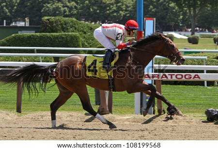 """SARATOGA SPRINGS - JUL 21: Alan Garcia gives """"Spurious Precision"""" a pat as the 2 year-old colt crosses the wire to win his first race at Saratoga Race Course on Jul 21, 2012 in Saratoga Springs, NY. - stock photo"""