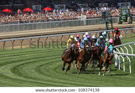 "SARATOGA SPRINGS - JUL 21: Horses take the club house turn in race 7 on Jul 21, 2012 at Saratoga Race Course in Saratoga Springs, NY. Eventual winner is Edgar Prado (pink cap) and ""Image of Disco"". - stock photo"