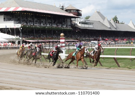 SARATOGA SPRINGS, NY - JULY 27: The field moves through the clubhouse turn in the third race on July 27, 2012 at Saratoga Springs, New York - stock photo