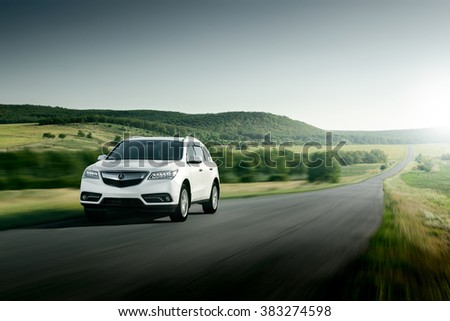 Saratov, Russia - August 11, 2015: Modern car Acura MDX fast drive on asphalt road at sunset - stock photo