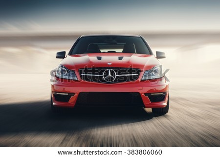 Saratov, Russia - August 24, 2014: Red Sport Car Mercedes-Benz C63 AMG Drive Speed On Asphalt Road At Sunset - stock photo