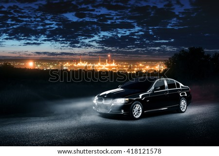 Saratov, Russia - June 12, 2015: Black car BMW E90 standing in the dark mist forest with views of the city at night - stock photo