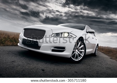 Saratov, Russia - October 16, 2014: Car Jaguar XJ staying on the road on dramatic clouds background - stock photo