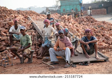 SARBERIA,INDIA, JANUARY 16: Brick field workers rest after hard work, wearing just baked brick from the kiln in truck on January 16, 2009 in Sarberia, West Bengal, India. - stock photo