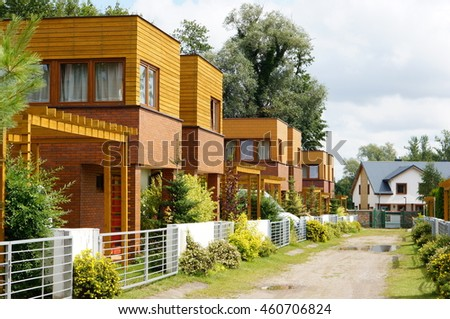 SARBINOWO, POLAND - JULY 29, 2016: Row of wooden holiday houses with parking place