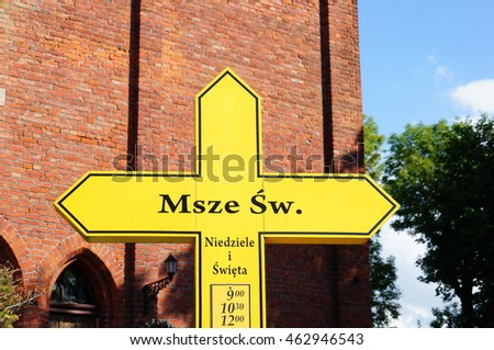SARBINOWO, POLAND - JULY 30, 2016: Yellow religious catholic cross in front of a building