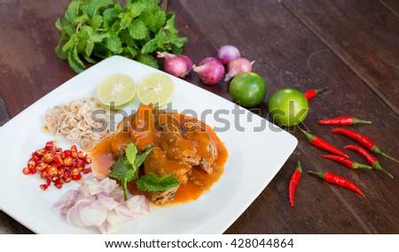 Sardines in Tomato Sauce Salad Thai-Style, lemongrass, chilli,lamon,onion,mint around white dish - stock photo