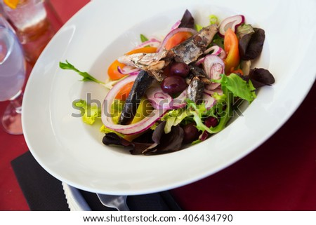 Sardines salad served with fresh veggies under sauce - stock photo