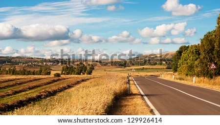 Sardinia, Trexenta, view of the road that runs along a field - stock photo