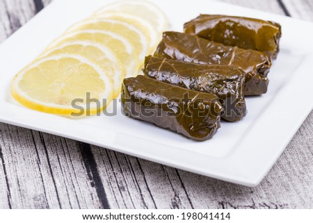 Sarma - Rice and Mint Wrapped in Grape Vine Leaves on a Rustic Table  - stock photo