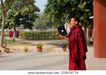 SARNATH, INDIA - JAN 5: Buddhist monk tries to take a picture of using a tablet computer Apple in the monastery on January 5, 2013. Sarnath is where Gautama Buddha first taught the Dharma at 500 BC.  - stock photo